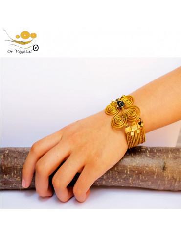 Bracelet en or végétal cerclé et tressé en papillon avec onyx au centre