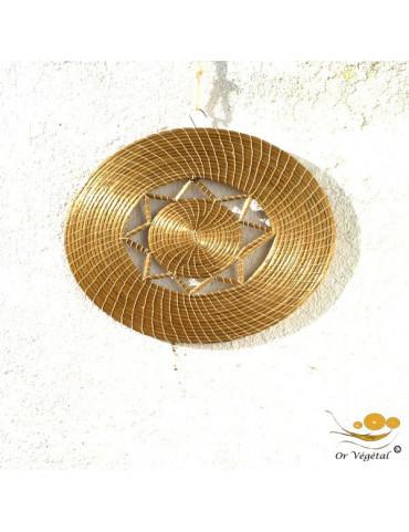 Décoration murale tréssé en or végétal de forme ronde évoquant le soleil